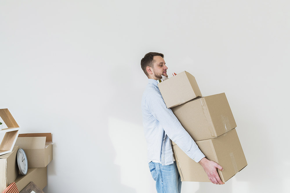 A white man carrying a stack of three moving boxes